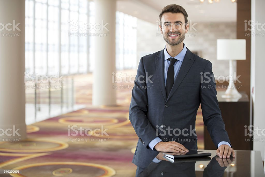 Portrait of young businessman with tablet in hotel lobby stock photo