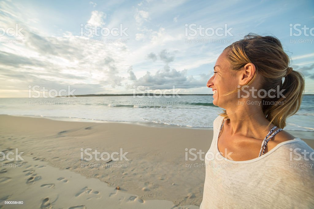 Portrait of young caucasian woman by the beach at sunset stock photo