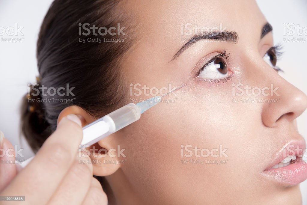 Portrait of young Caucasian woman getting cosmetic injection stock photo