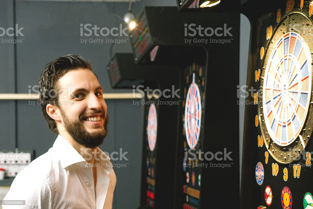 Portrait Of Young Cheerful Man Playing Darts stock photo