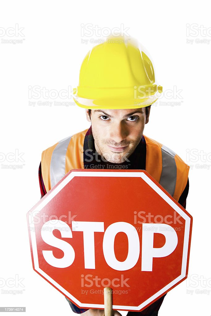 Portrait of  young  construction worker holding a stop sign royalty-free stock photo