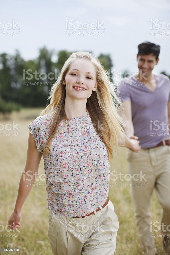 Portrait of young couple holding hands in rural field royalty-free stock photo