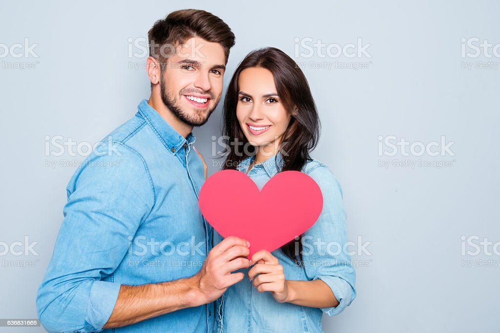 Portrait of young couple in love holding red paper heart stock photo
