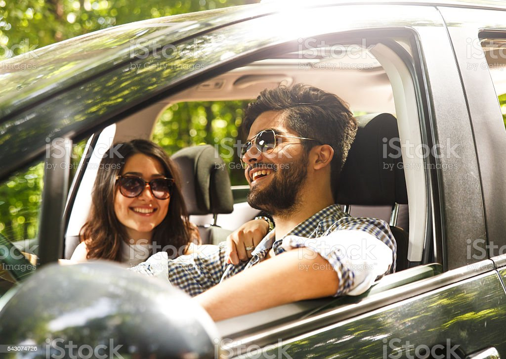 Portrait of young couple sitting in car stock photo