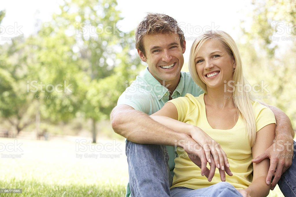 Portrait Of Young Couple Sitting In Park royalty-free stock photo