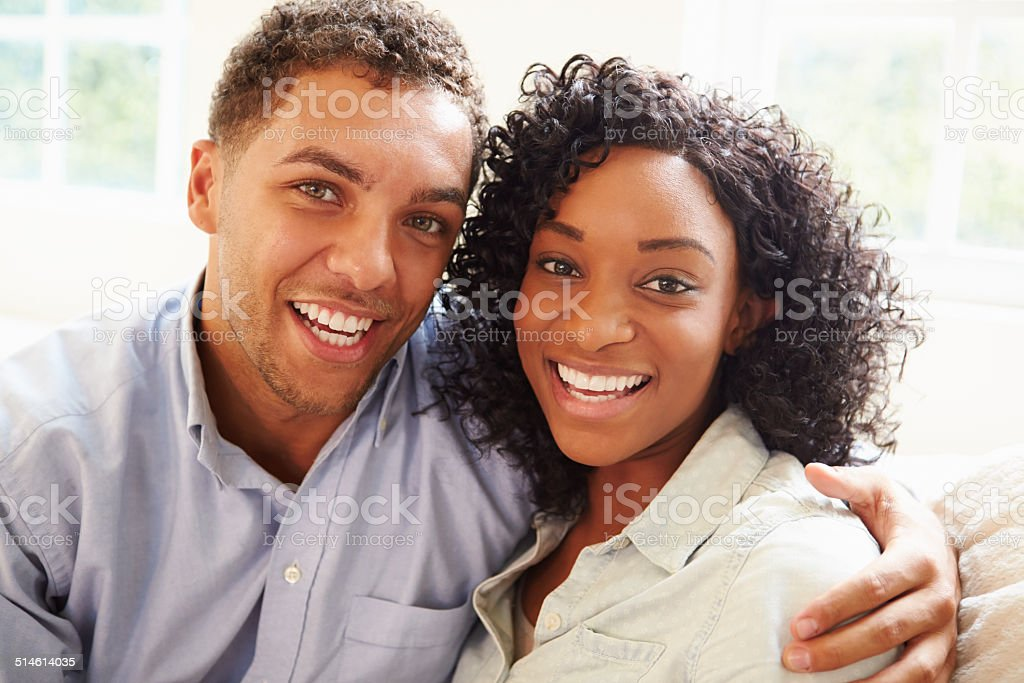 Portrait Of Young Couple Sitting On Sofa At Home stock photo