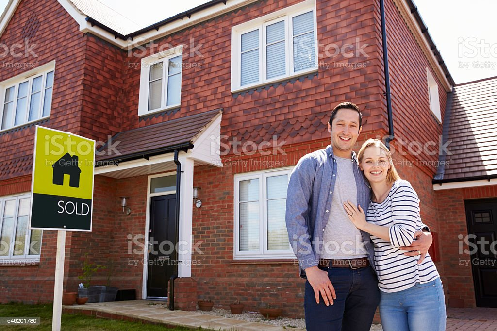 Portrait Of Young Couple Standing Outside New Home stock photo
