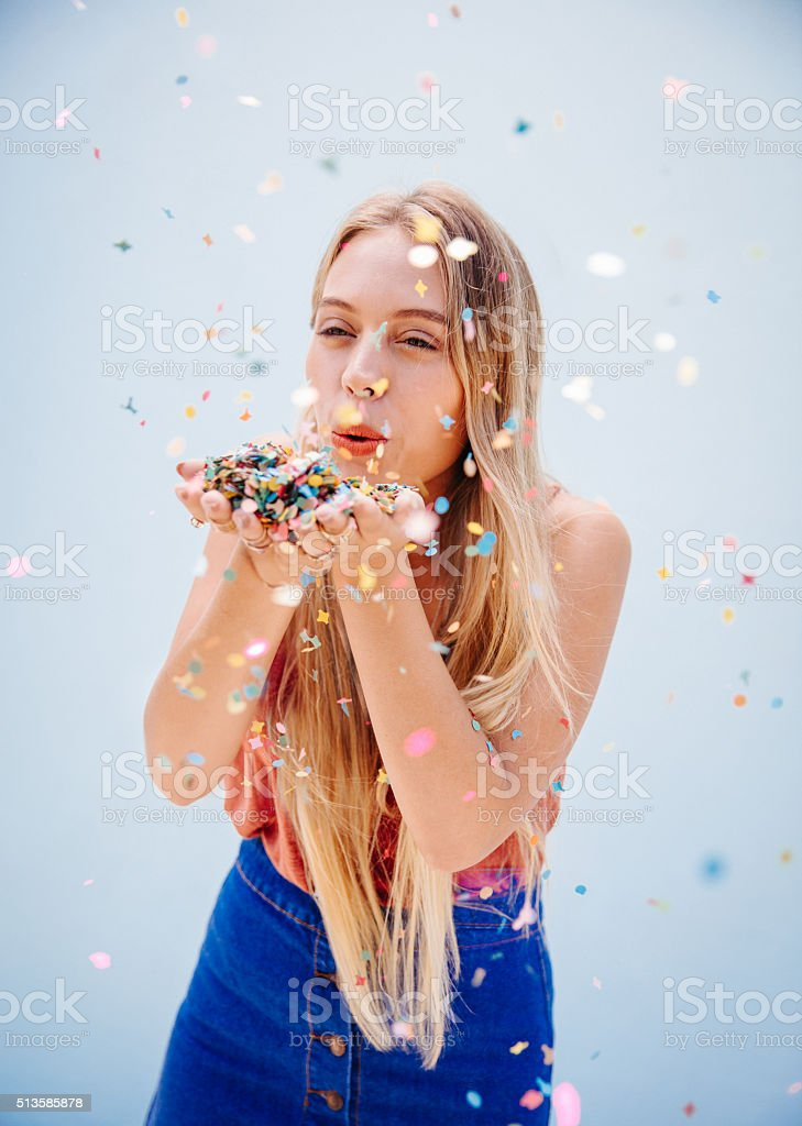 Young teenager girl blowing colorful confetti, isolated on blue wall...
