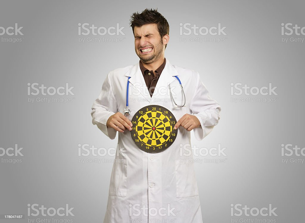 Portrait Of Young Doctor Holding A Dartboard stock photo