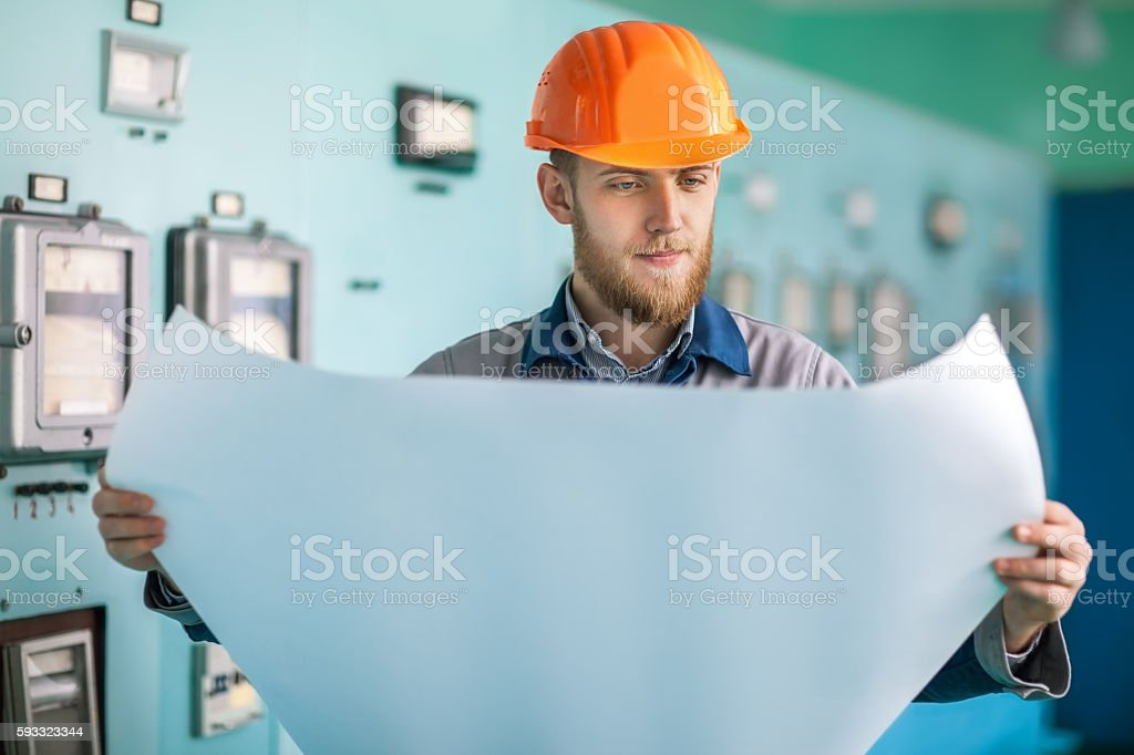 Portrait of young engineer working with blueprint stock photo