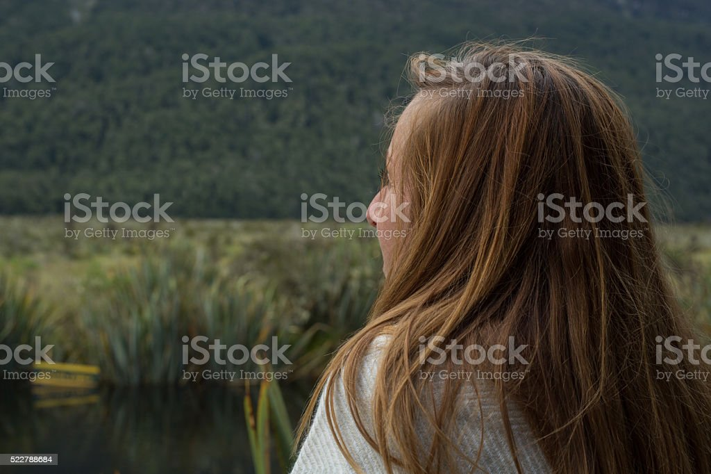 Portrait of young female looking at beautiful mountain lake landscape stock photo