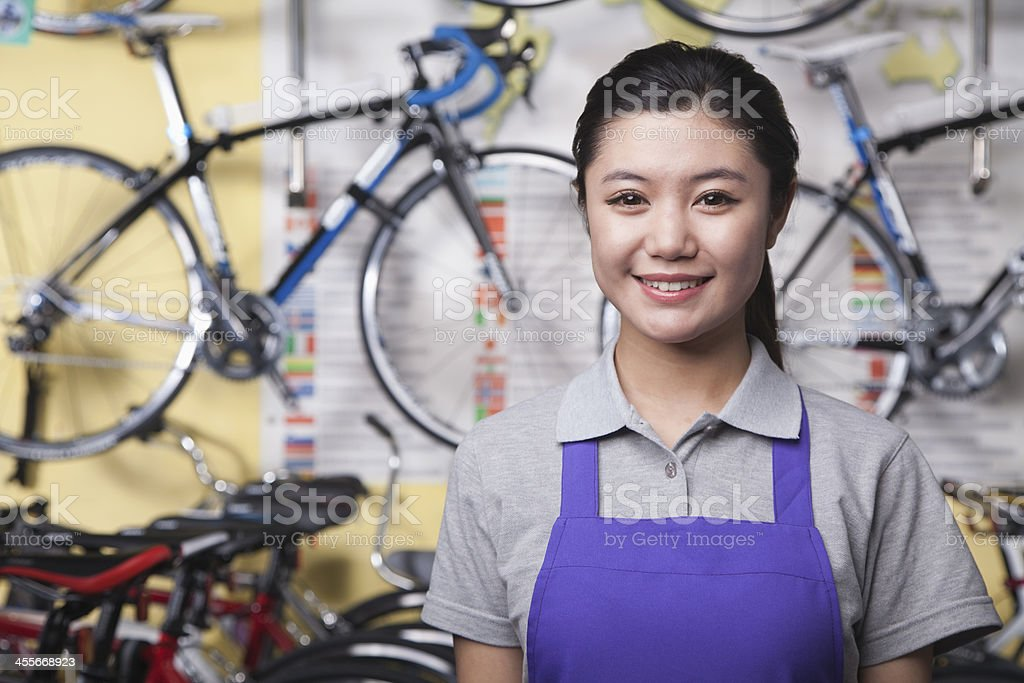 Portrait of young female mechanic in bicycle store, Beijing stock photo