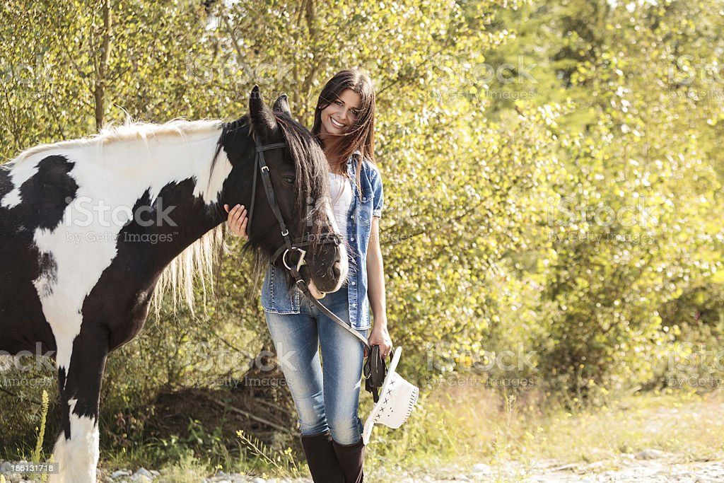 portrait of young female rider smiling and embracing her horse royalty-free stock photo
