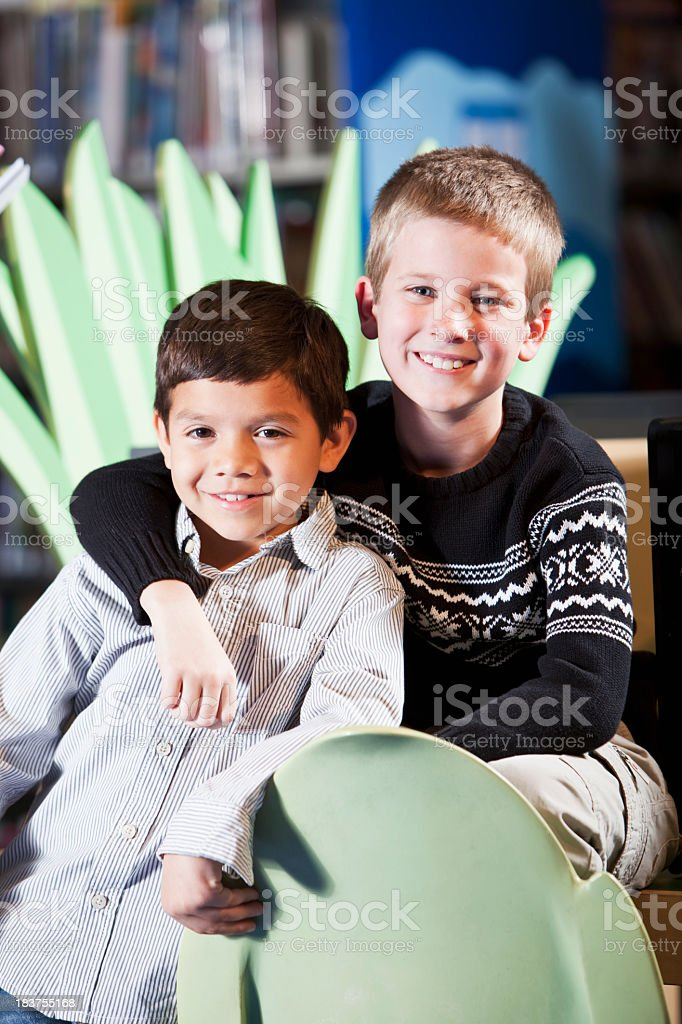 Portrait of young friends in library stock photo