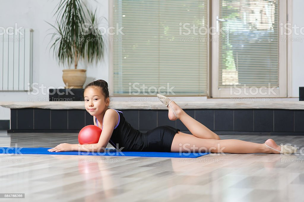 Portrait of Young girl gymnast with red ball. stock photo