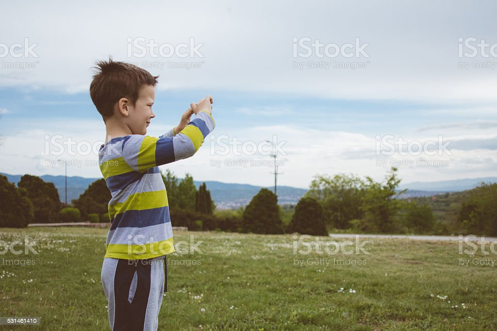 Portrait of young handsome boy taking picture at the park stock photo