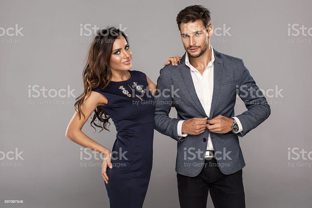 Portrait of young handsome man buttoning jacket with woman stock photo