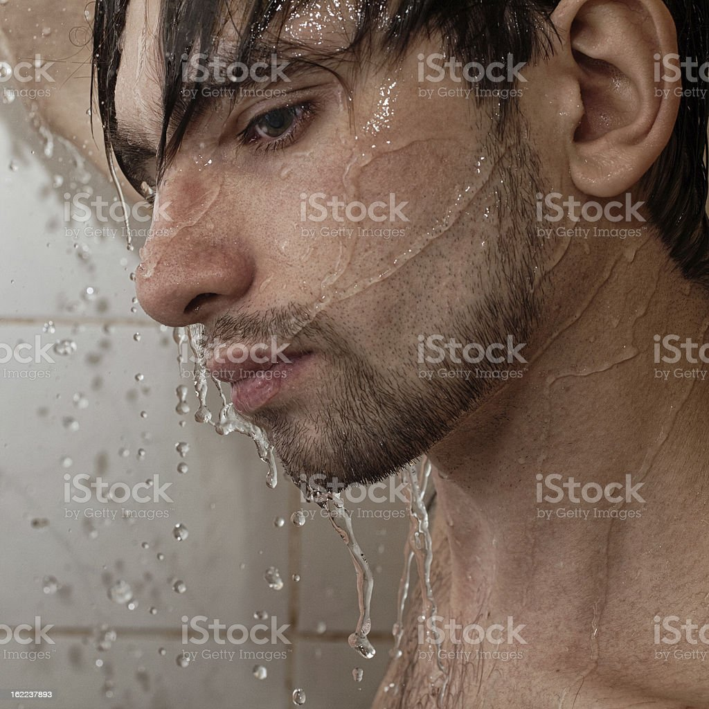 Portrait of  young handsome man takes shower royalty-free stock photo