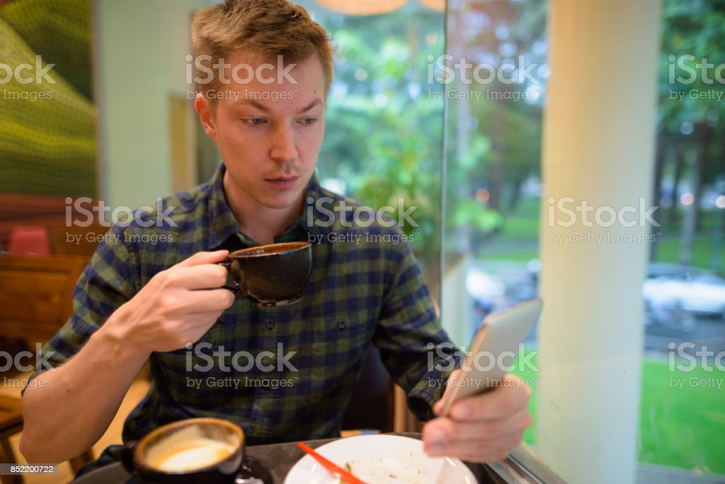 Portrait of young handsome tourist man relaxing inside the coffee...