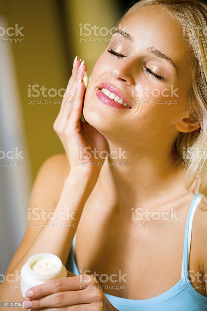 Portrait of young happy smiling beautiful woman applying creme royalty-free stock photo