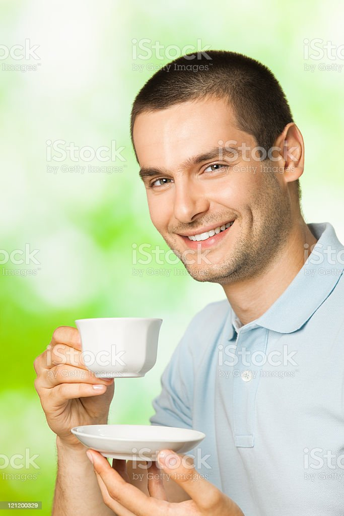 Portrait of young happy smiling man drinking coffee, outdoors stock photo