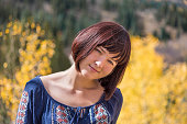 Portrait of young happy smiling woman by autumn aspen trees