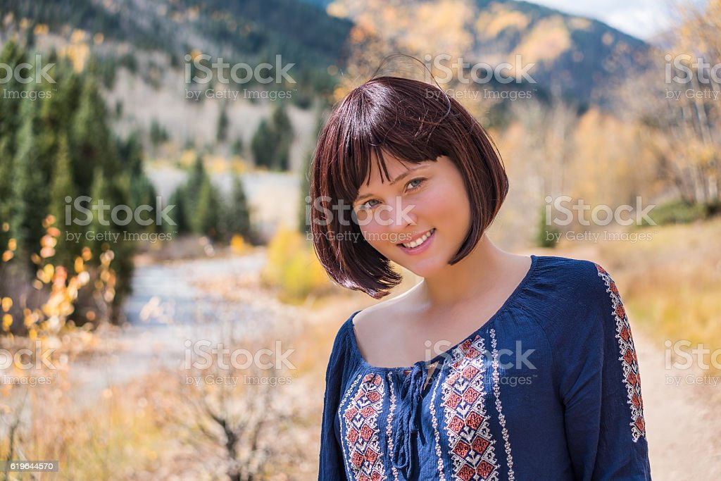 Portrait of young happy smiling woman by autumn river stock photo
