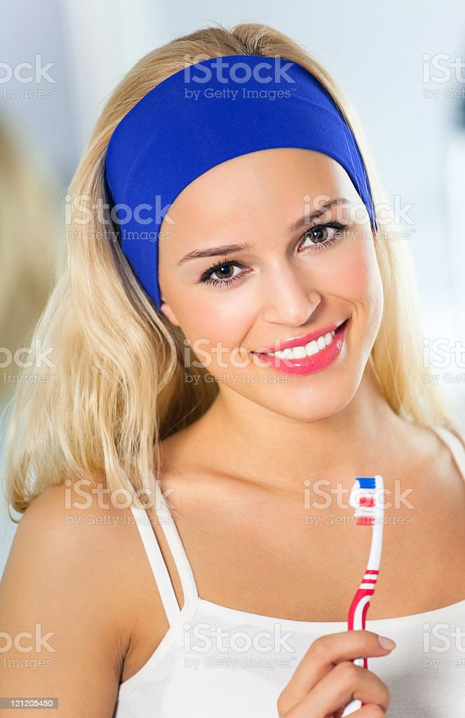 Portrait of young happy smiling woman with toothbrush at bathroom stock photo