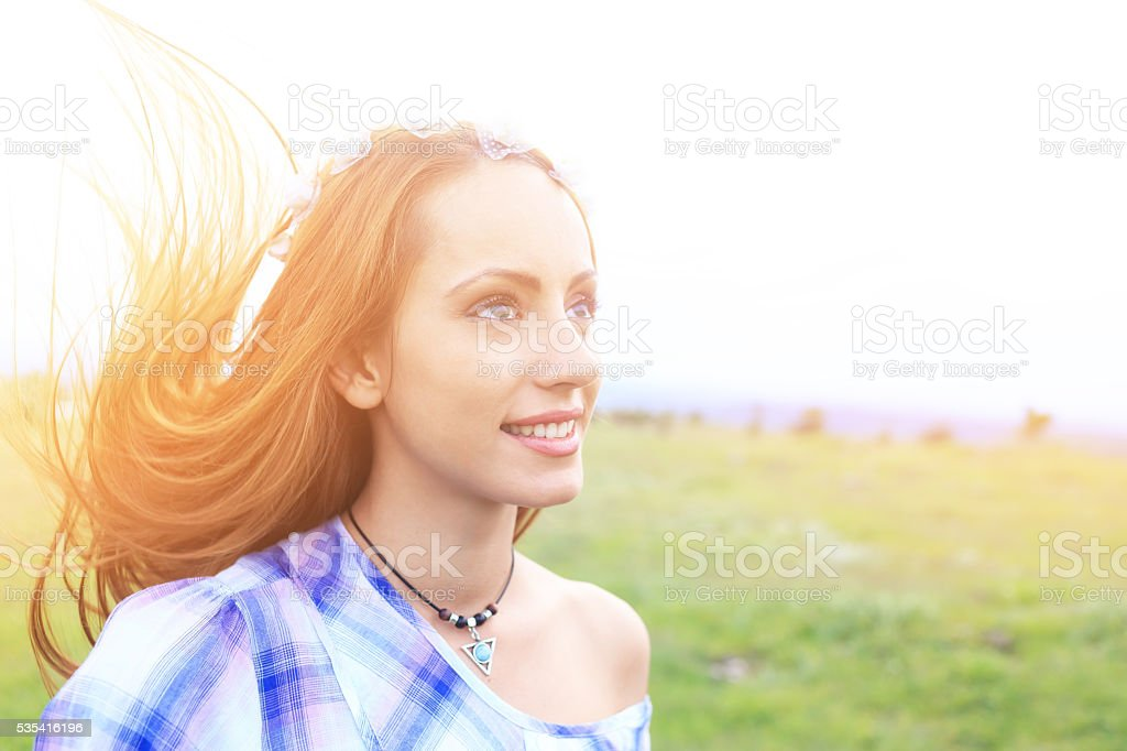 Portrait of young hippie woman with wreath on field stock photo