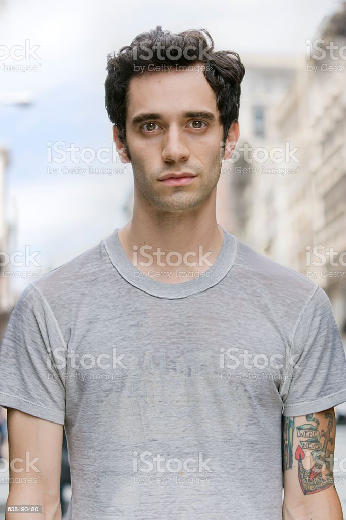 Portrait of young Hispanic man in downtown city stock photo
