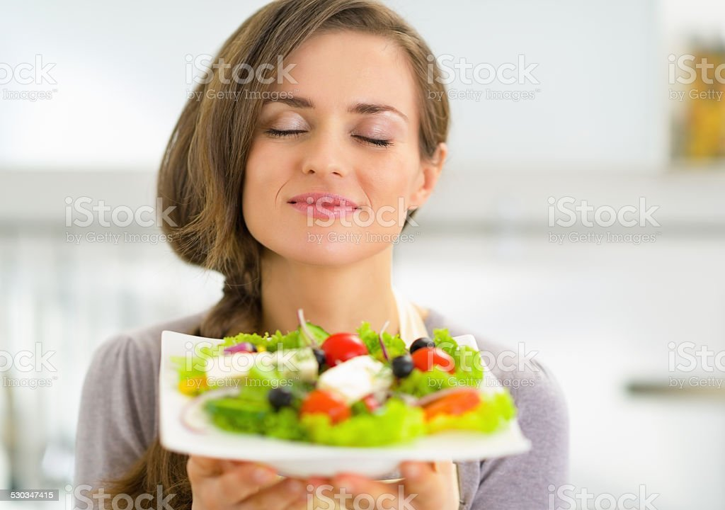 portrait of young housewife enjoying fresh salad stock photo