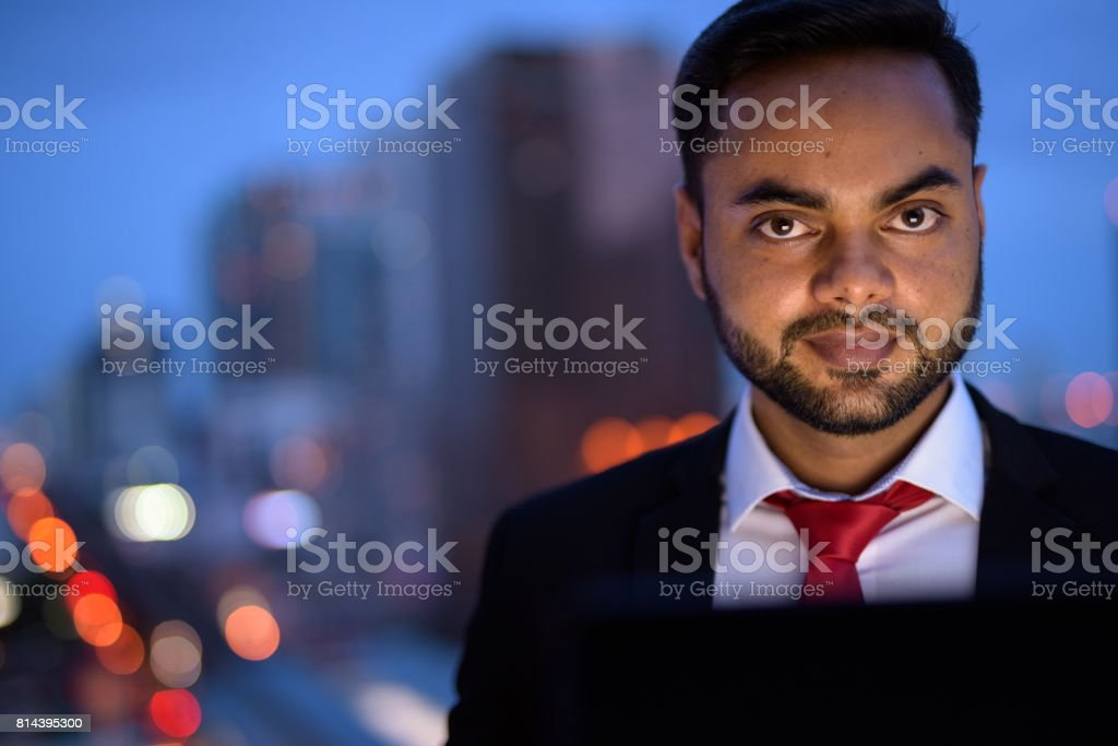 Portrait of young Indian businessman against view of the city in Bangkok Thailand stock photo