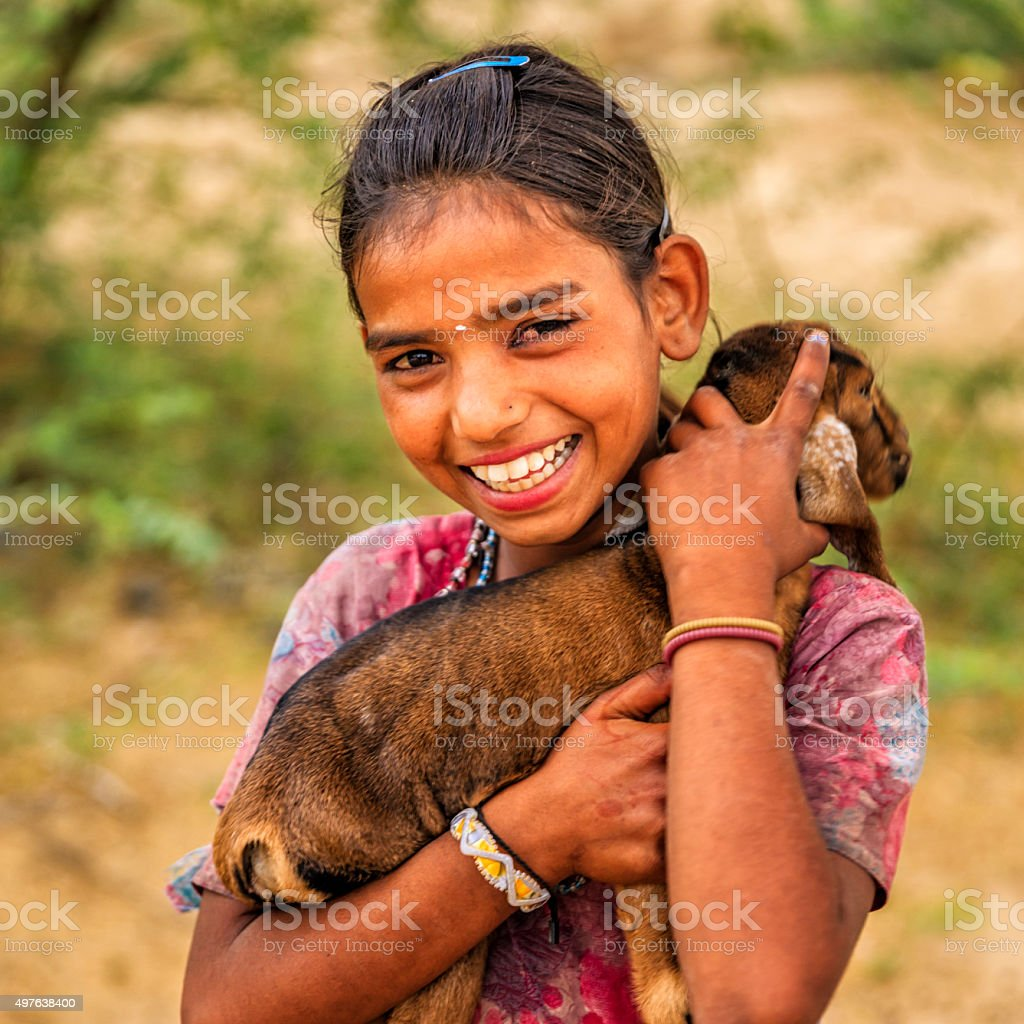 Portrait of young Indian girl holding goat, village near Jodhpur stock photo