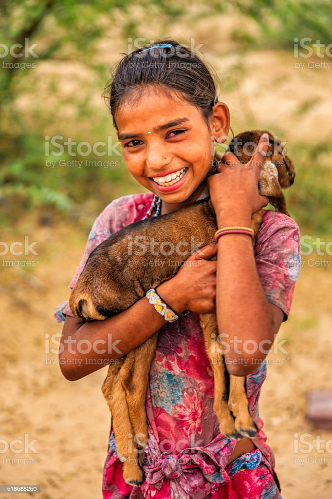 Portrait of young Indian girl holding goat, village near Jodhpur stock photo