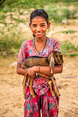 Portrait of young Indian girl holding goat, village near Jodhpur