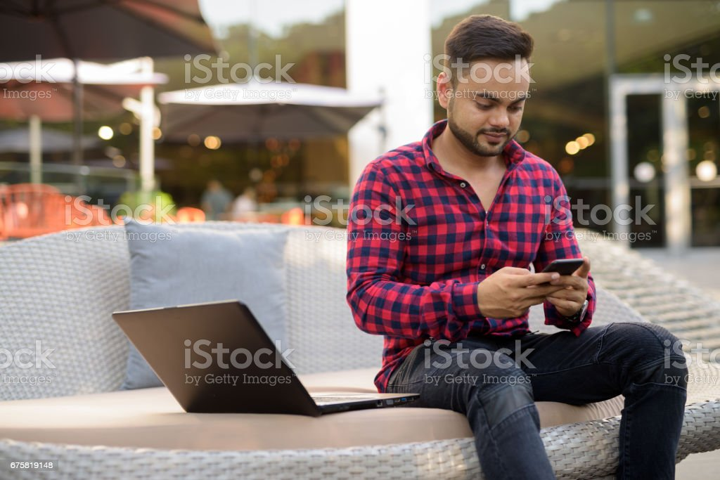 Portrait of young Indian man enjoying life in Siam Square at Bangkok Thailand stock photo