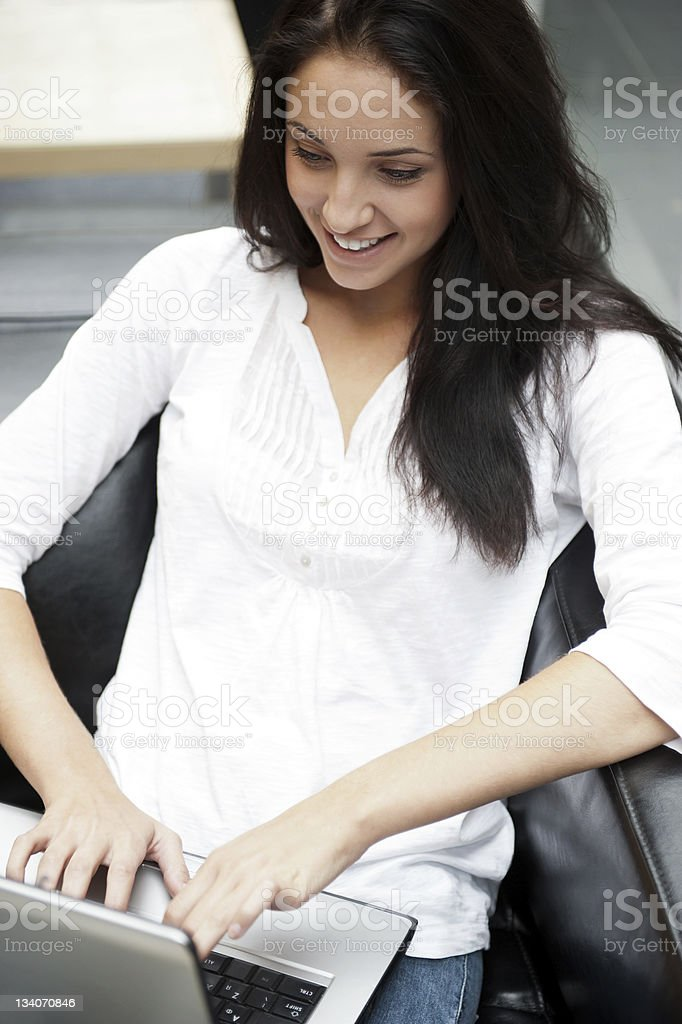 Portrait of young lady with long dark hair working on laptop royalty-free stock photo