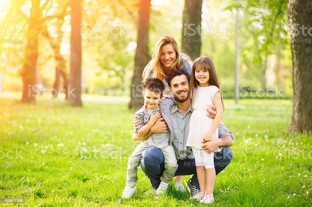 Portrait of young loving family in the park. stock photo