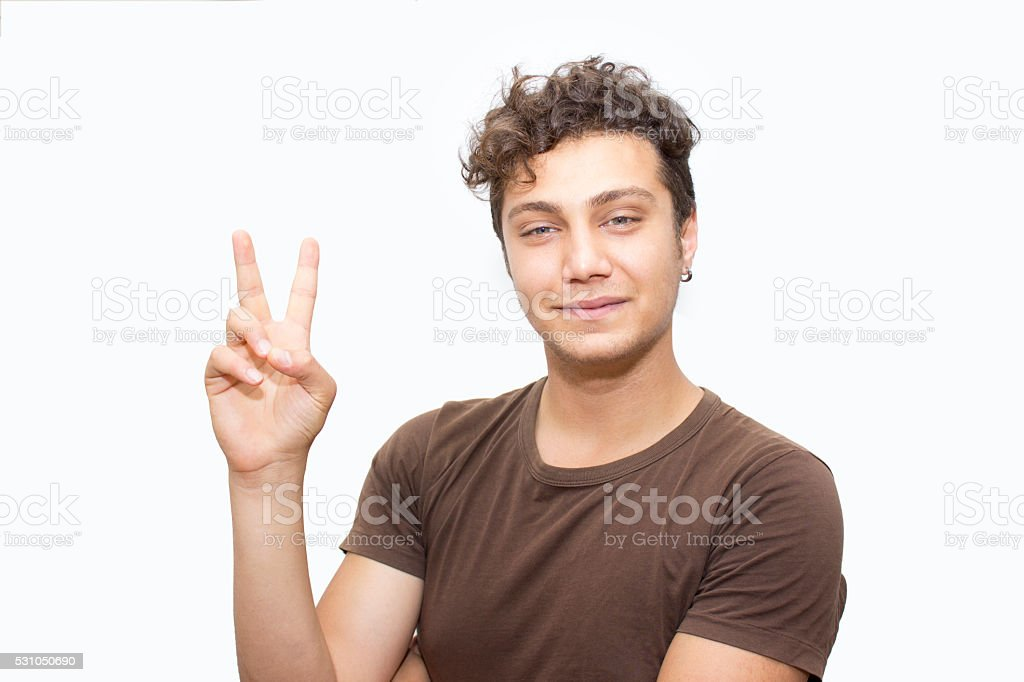 Portrait of young man gesturing peace sign stock photo