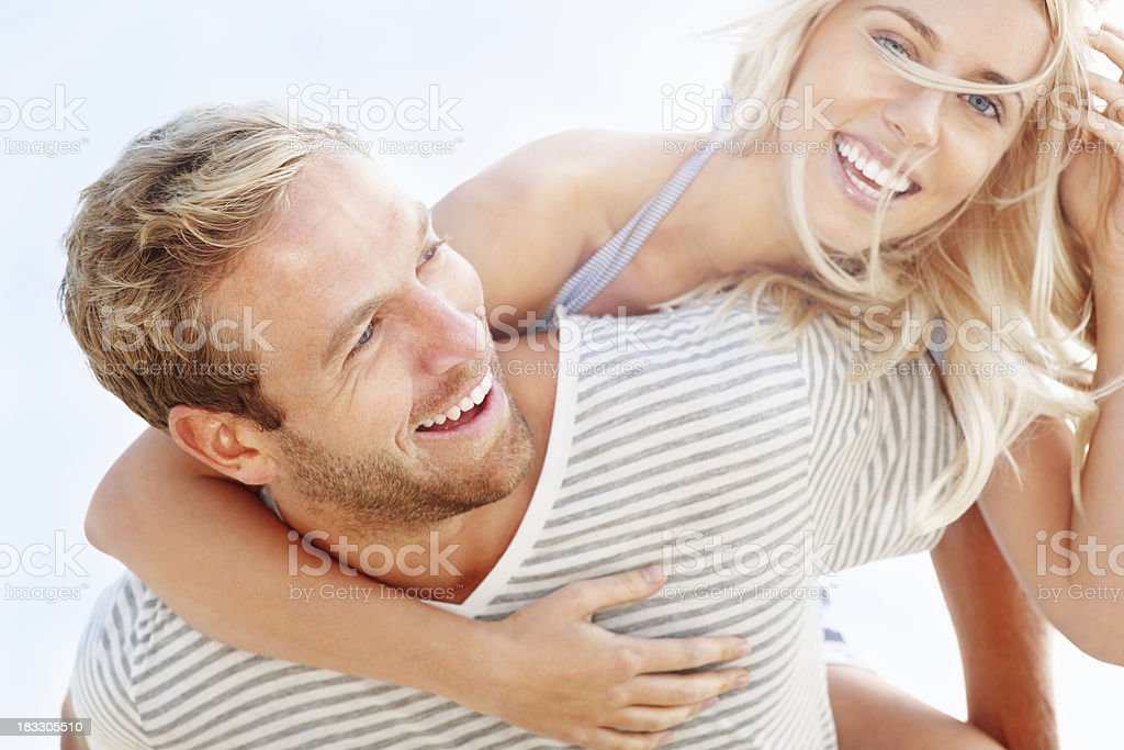 Portrait of young man giving his girlfriend a piggybackride stock photo
