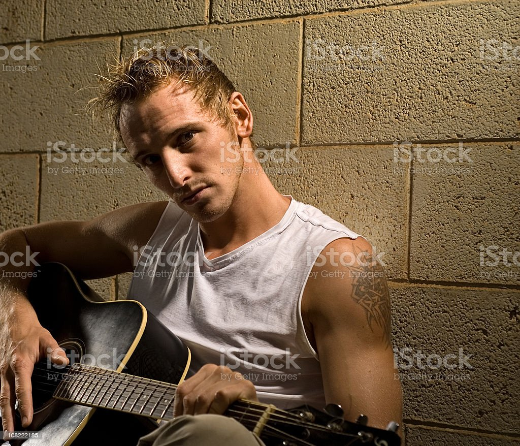 Portrait of Young Man Holding Guitar and Leaning Against Wall royalty-free stock photo
