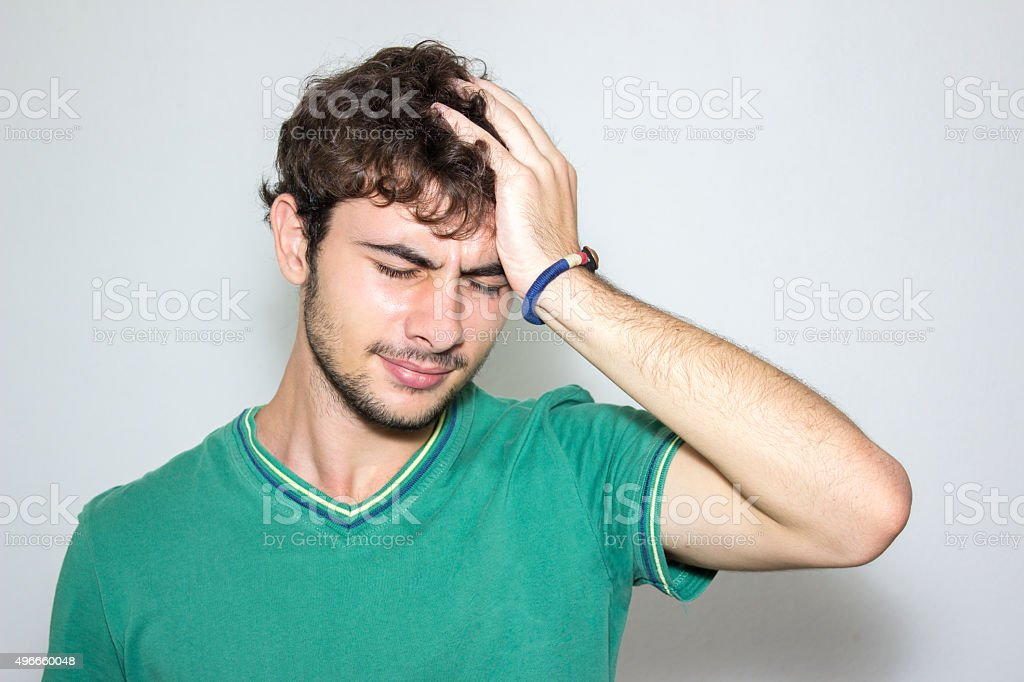 Portrait of young man holding his head in pain stock photo