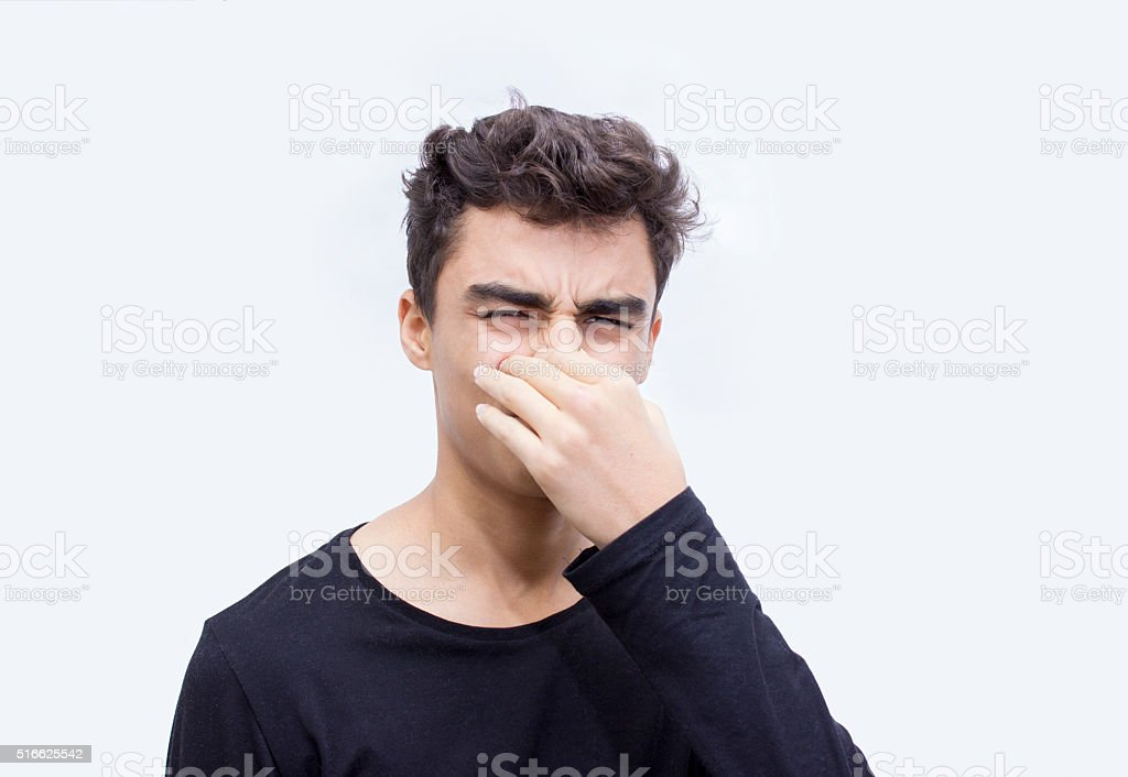 Portrait of young man holding his nose in worry stock photo