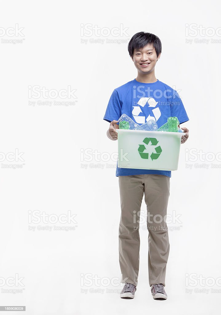 Portrait of young man holding recycling bin, studio shot royalty-free stock photo