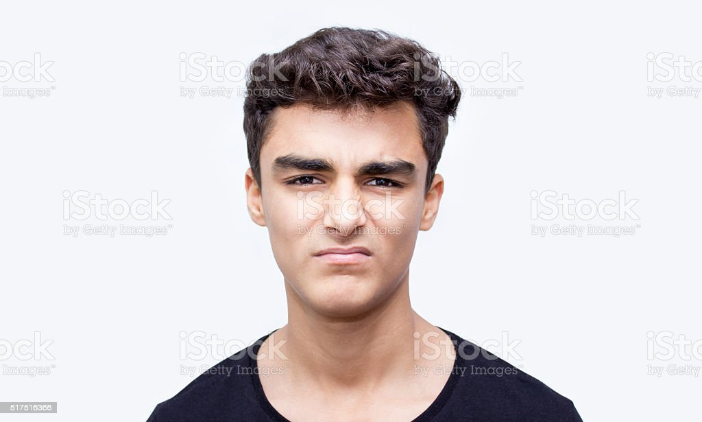 Portrait of young man in disgust expression over white background stock photo