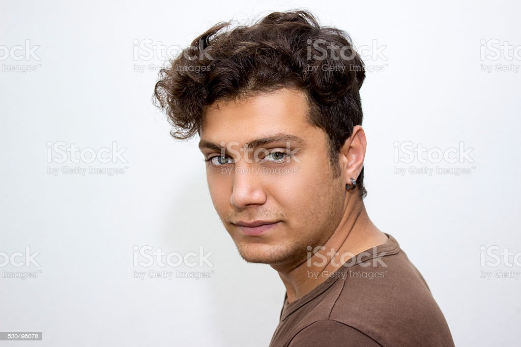 Portrait of young man looking at camera over beige background stock photo