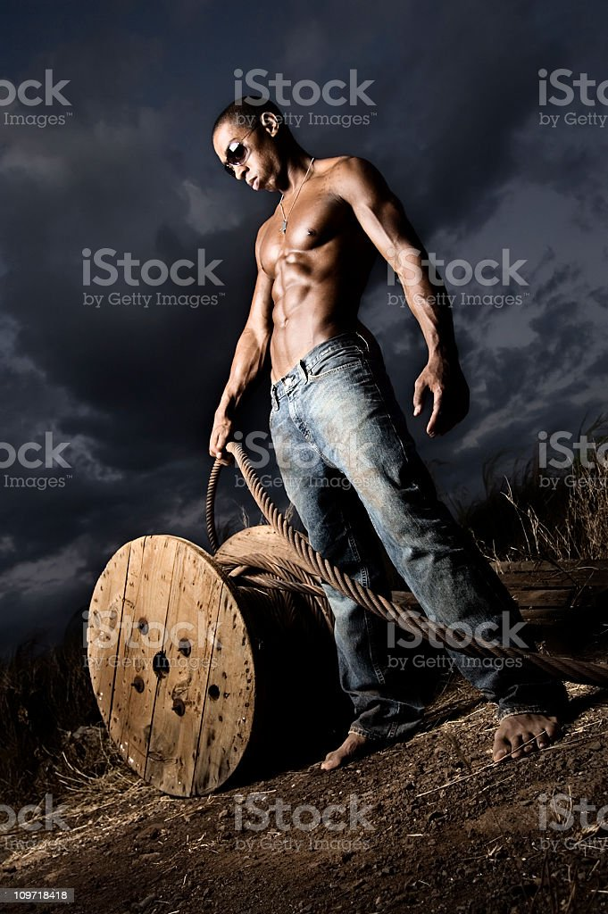 Portrait of Young Man Pulling on Cables at Dusk royalty-free stock photo