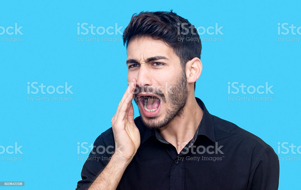 Portrait of young man shouting against blue background stock photo