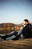 Portrait of young man sitting and relax on the pier