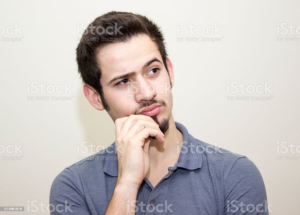 Portrait of young man thinking over colored background stock photo